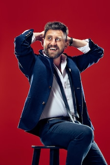 Homem de negócios feliz sentado e sorrindo, isolado no fundo vermelho do estúdio.