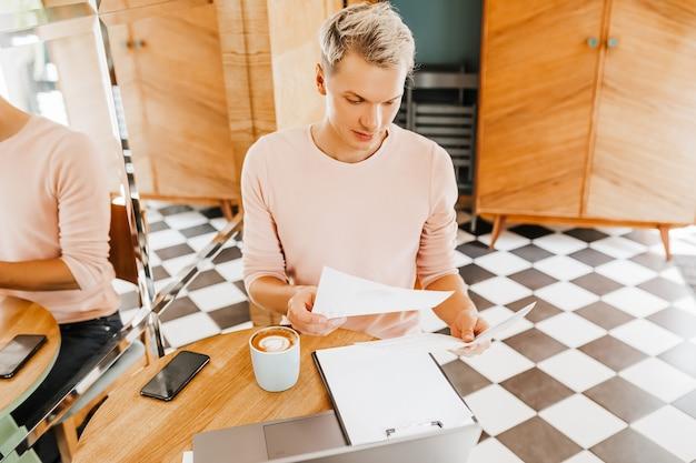 Homem de negócios feliz sentado na cafeteria com laptop e documentos