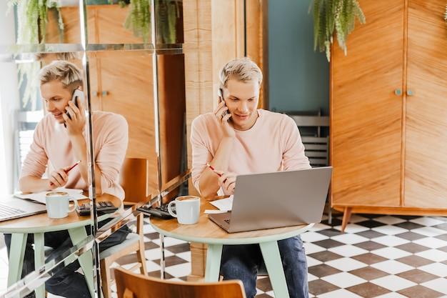 Homem de negócios feliz sentado na cafeteria com laptop e smartphone