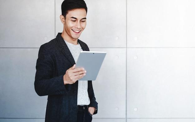 Homem de negócios feliz using digital tablet. lendo dados e sorrindo