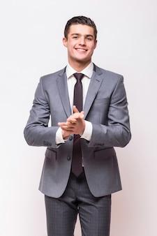 Homem de negócios feliz vestindo terno cinza isolado na parede branca