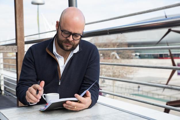 Homem de negócios focalizado, verificando o planejador diário