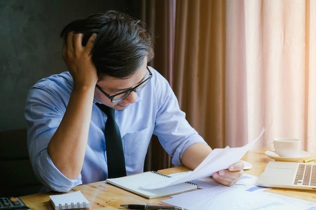 Homem de negócios forçado. um homem novo senta-se em sua mesa e guarda suas mãos em sua cabeça por causa do esforço e do relatório sumário.