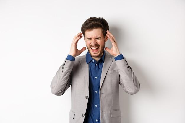 Homem de negócios frustrado de terno enlouquecendo, gritando e apertando as mãos perto da cabeça