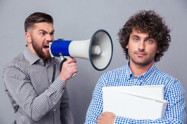 Homem de negócios furioso gritando via megafone para outro homem por cima de uma parede cinza