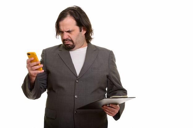 Homem de negócios gordo e caucasiano parecendo confuso enquanto usa o celular e segura a prancheta