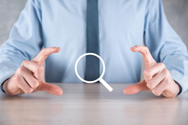Homem de negócios, homem segura na mão lupa icon.business, tecnologia e conceito de internet