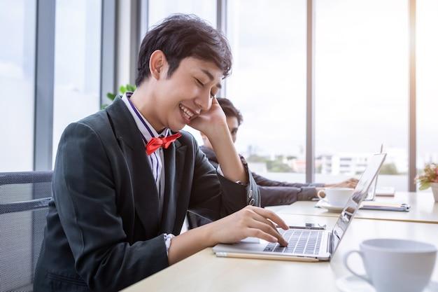 Homem de negócios homossexual asiático lgbt falando com o celular enquanto trabalhava no computador laptop e grupo de executivos na sala de reuniões de um escritório moderno