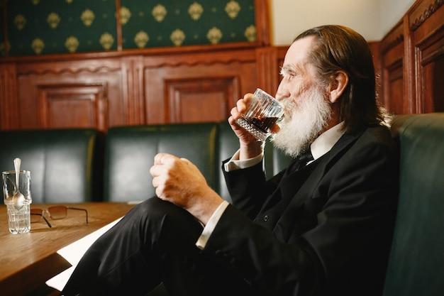 Homem de negócios idoso barbudo. homem bebe uísque. sênior em um terno preto.