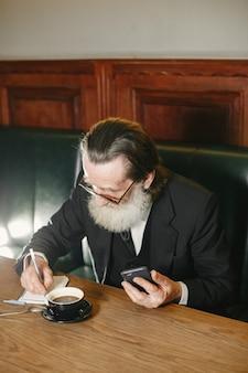 Homem de negócios idoso barbudo. homem com café. sênior em um terno preto.