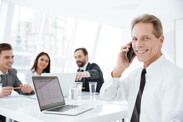 Homem de negócios idoso de terno sentado à mesa no escritório com colegas e falando ao telefone