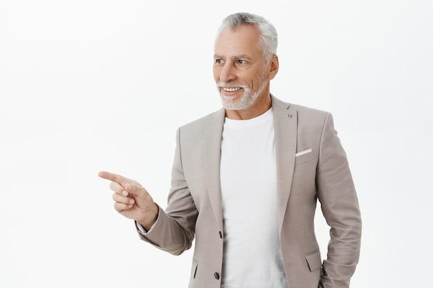 Homem de negócios idoso e bem-sucedido apontando o dedo para a esquerda