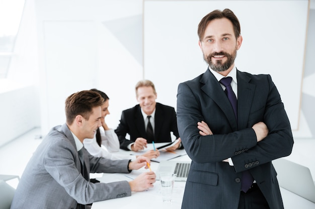 Homem de negócios idoso em pé perto da mesa com os braços cruzados e com parceiros de negócios