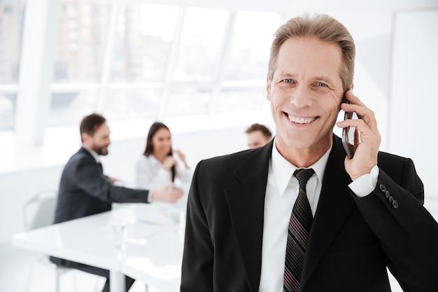 Homem de negócios idoso falando ao telefone no escritório com colegas perto da mesa