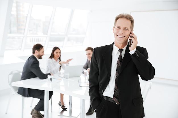 Homem de negócios idoso feliz falando ao telefone no escritório com colegas