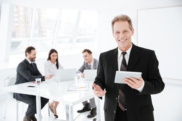 Homem de negócios idoso segurando um tablet no escritório com colegas perto da mesa