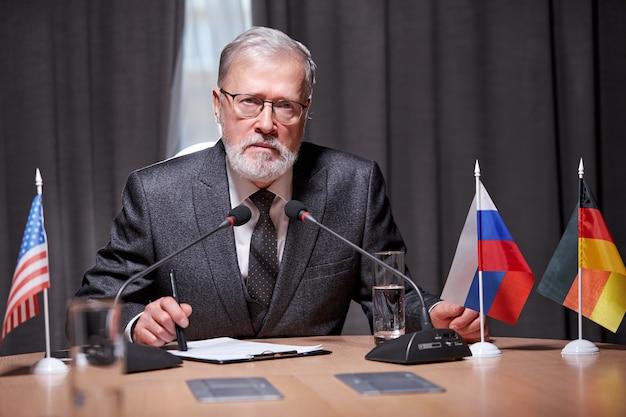 Homem de negócios idoso sentado com um microfone na moderna sala de reuniões durante uma reunião com parceiros de negócios, um homem bonito de óculos falando com confiança, vestindo um terno formal
