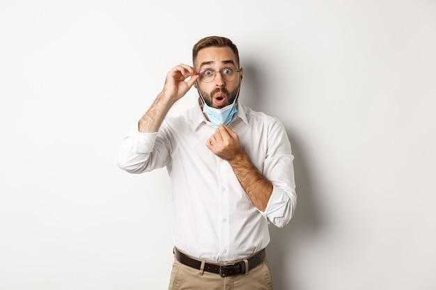 Homem de negócios impressionado tirando máscara médica, parecendo surpreso, de pé