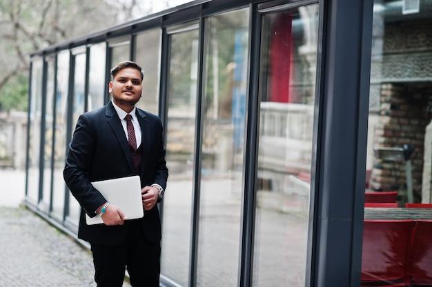 Homem de negócios indiano à moda com roupa formal com o laptop nas mãos de pé contra janelas no centro de negócios.