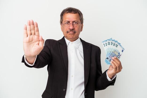 Homem de negócios indiano envelhecido médio segurando contas isoladas no fundo branco, de pé com a mão estendida, mostrando o sinal de stop, impedindo-o.