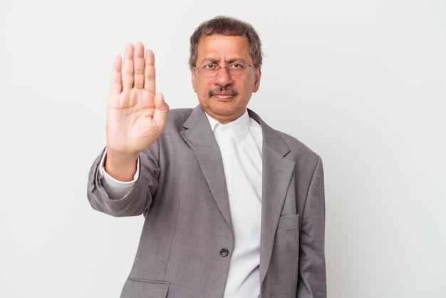 Homem de negócios indiano envelhecido meio isolado no fundo branco, de pé com a mão estendida, mostrando o sinal de pare, impedindo-o.