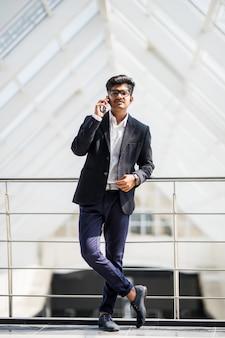 Homem de negócios indiano jovem em um telefone no telefone