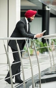 Homem de negócios indiano novo no escritório moderno com tabuleta.