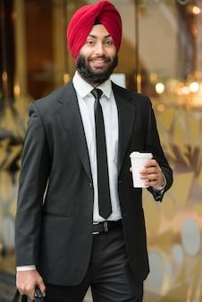 Homem de negócios indiano novo no turbante com café.