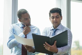 Homem de negócios indiano novo que lê o documento em voz alta para o colega de trabalho
