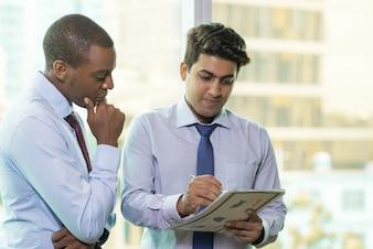 Homem de negócios indiano novo que mostra o relatório financeiro ao colega de trabalho