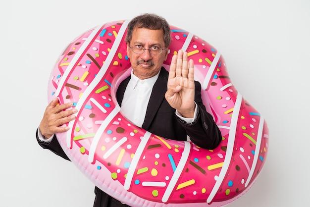 Homem de negócios indiano sênior segurando donut inflável isolado no fundo branco, de pé com a mão estendida, mostrando o sinal de stop, impedindo-o.