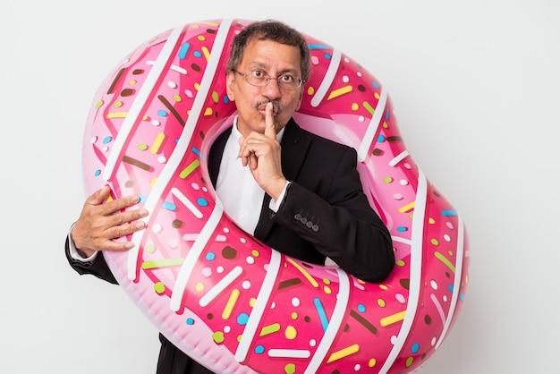 Homem de negócios indiano sênior segurando donut inflável isolado no fundo branco, mantendo um segredo ou pedindo silêncio.