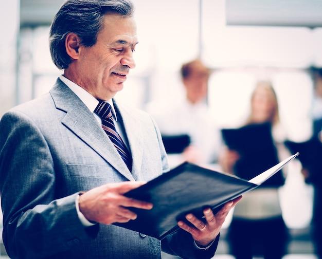 Homem de negócios inteligente e feliz com colegas de equipe discutindo em segundo plano