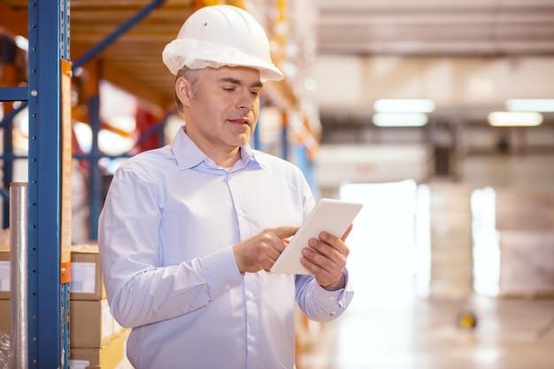 Homem de negócios inteligente e simpático usando o tablet enquanto está em seu armazém