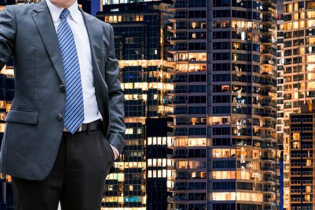 Homem de negócios inteligente em pé no fundo de iluminação do prédio de escritórios