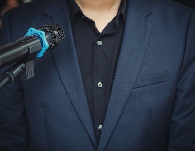 Homem de negócios inteligente falando e falando com microfones na sala de seminário ou na sala de conferências falando