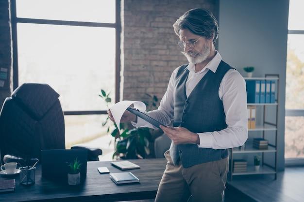 Homem de negócios inteligente focado lendo a prancheta no escritório
