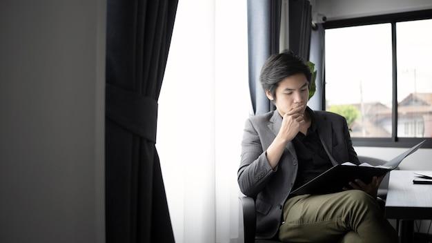 Homem de negócios inteligente sentado no moderno local de trabalho.