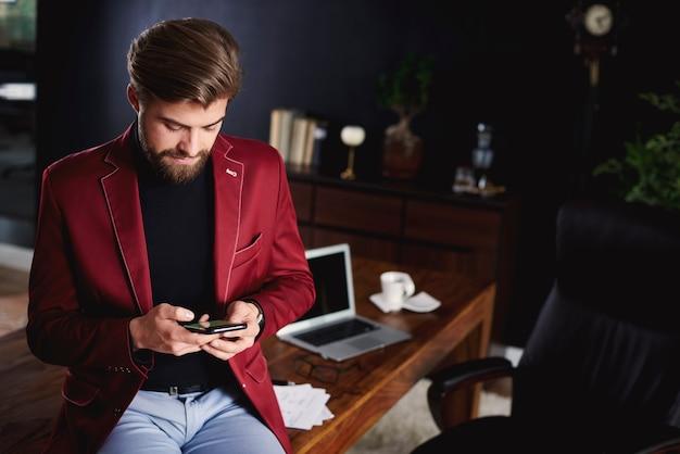 Homem de negócios inteligente usando smartphone durante uma pequena pausa