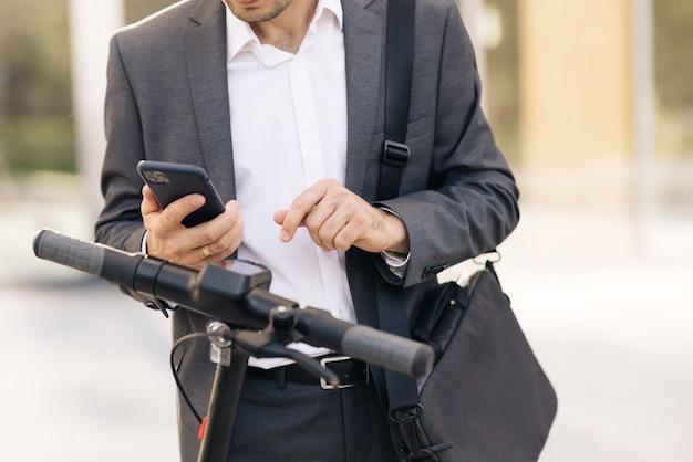 Homem de negócios irreconhecível de terno está se preparando para alugar um aplicativo de telefone scooter elétrico