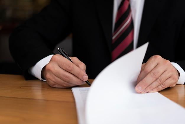 Homem de negócios irreconhecível, escrevendo a vista frontal