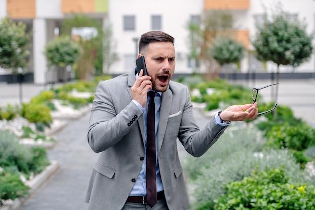 Homem de negócios irritado no vestuário formal que grita sobre o telefone esperto em seu empregado ao estar ao ar livre.