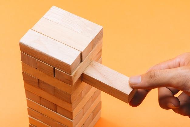 Homem de negócios jogando um bloco de madeira em uma torre
