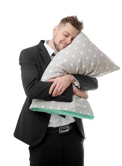Homem de negócios jovem abraçando o travesseiro e continuando a dormir, isolado no branco