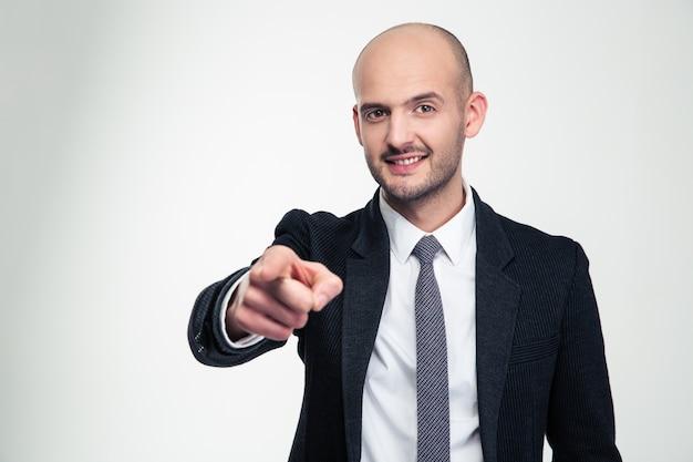 Homem de negócios jovem alegre atraente em trajes formais apontando para você sobre uma parede branca