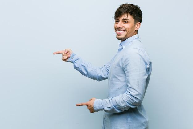 Homem de negócios jovem animado apontando com o dedo indicador fora