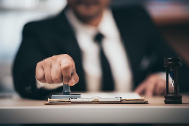 Homem de negócios jovem appoval stamper carimbo no contrato comercial de papel, dinheiro de empréstimo aprovado.