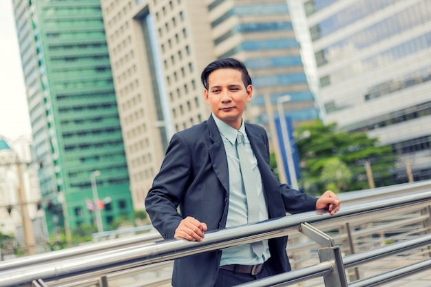 Homem de negócios jovem ásia na frente do edifício moderno no centro da cidade conceito de jovens empresários