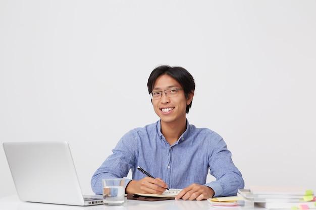 Homem de negócios jovem asiático feliz bonito em copos, escrevendo no caderno, trabalhando com o laptop na parede branca