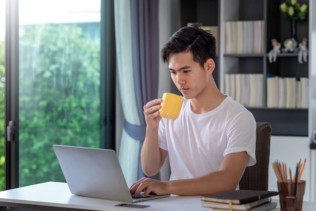 Homem de negócios jovem asiático trabalhando em casa usando um laptop e bebendo café na mesa.